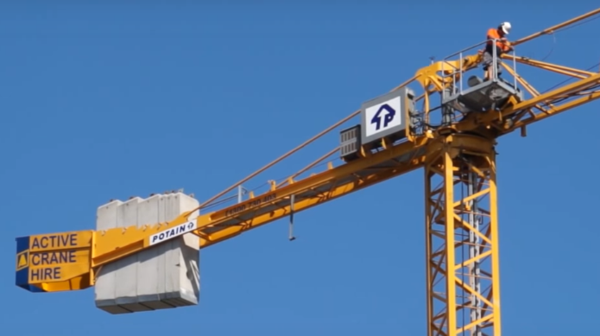 Man working atop a Potain crane jib